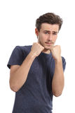 Casual young man ready to fight defending with fist up stock photo