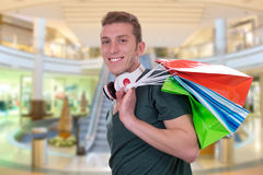 Casual young man with shopping bags in a mall Royalty Free Stock Photos