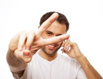 Casual young man showing thumbs up sign Stock Photos