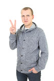 Casual young man showing a victory sign Royalty Free Stock Images