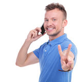 Casual young man shows victory over the phone Royalty Free Stock Image