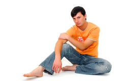Casual young man sitting on the floor. Casual young man in orange t-shirt sitting on white backdrop. Full body shot in studio over white Royalty Free Stock Images