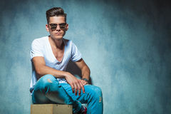 Casual young man sitting on a wood box Royalty Free Stock Photos