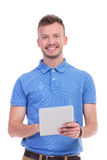 Casual young man smiles while holding tablet Stock Image