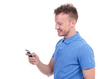 Casual young man smiles while texting Stock Photos