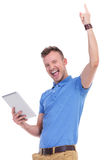 Casual young man with tablet cheers Royalty Free Stock Photography
