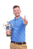 Casual young man with trophy shows victory sign Stock Images