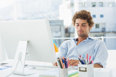 Casual young man using computer in bright office Royalty Free Stock Photography