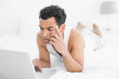 Casual young man using laptop in bed Stock Photo