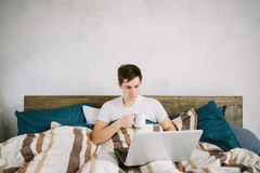 Casual young man using laptop in bed at home and drinking coffee Royalty Free Stock Images