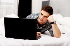 Casual young man using laptop in bed at home. Royalty Free Stock Images