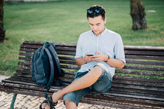 Casual young asian man using smart phone sitting on bench in cit Stock Images