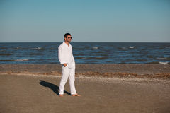 Casual young man walking on sea shore Stock Photography