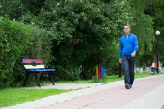 Casual young man walking in the summer park Stock Images