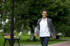 Casual young man walking in the summer park Royalty Free Stock Photo