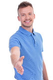 Casual young man wants to shake hands with you Stock Photography