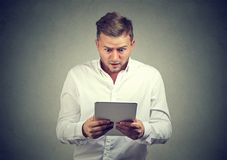 Shocked man exploring news in tablet. Casual young man watching tablet with feeling of puzzlement standing on gray background Royalty Free Stock Image