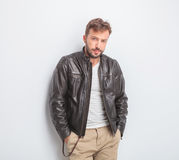 Casual young man wearing leather jacket is standing Royalty Free Stock Photography