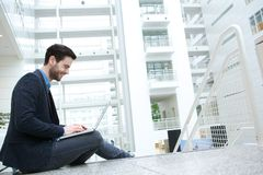 Casual young man working on laptop Stock Images