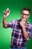 Casual young man writing with marker. On green background Stock Photos