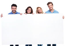 Casual young people showing a big blank banner and smile Royalty Free Stock Photos