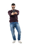 Casual young tourist taking picture with cellphone aiming at camera. Full body length portrait isolated over white studio background royalty free stock photography