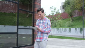 Casual Young Walking Man Using Tablet PC. Creative designer , businessman stock footage