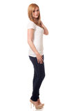 Casual Young Woman. Young woman in white t-shirt and jeans. Studio shot over white Stock Images
