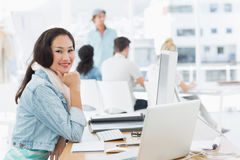 Casual young woman with colleagues behind in office Stock Photography