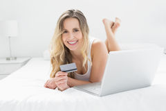 Casual young woman doing online shopping in bed Royalty Free Stock Images