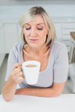 Casual young woman drinking coffee in kitchen Royalty Free Stock Images