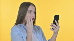 Casual Young Woman Facing Loss on Smartphone, Yellow Background