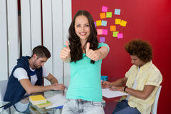 Casual young woman gesturing thumbs up Stock Photo
