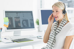 Casual young woman with headset in office. Side view of a casual young women with headset sitting by computers in a bright office Stock Photos