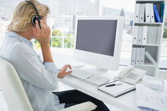 Casual young woman with headset using computer. Side view of a casual young woman with headset using computer in a bright office Royalty Free Stock Photography