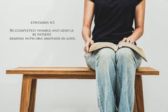 Casual young woman holds an open Bible Ephesians 4:2 on her lap. Stock Photos