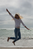 Casual young woman jumping at beach Stock Photography
