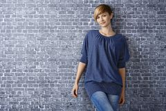 Casual young woman leaning to wall. Portrait of casual young woman leaning to grey brick wall, smiling Stock Photography