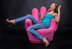 Casual young woman listening to mp3 player. Royalty Free Stock Image