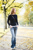 Casual Young Woman in a Park in the Fall Royalty Free Stock Photo