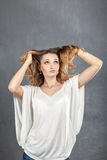 Casual young woman plaing with hair Stock Image