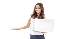 Casual young woman presenting copy space while holding a laptop Stock Image