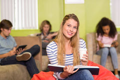 Casual young woman reading book in office Royalty Free Stock Photography
