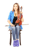 Casual young woman seated on a wooden chair holding a violin Stock Photos