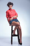 Casual young woman sits on chair Stock Photo
