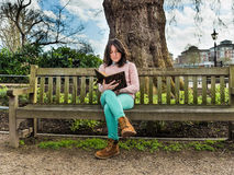 A Casual Young Woman Sitting on a Bench in a Park and Reading Royalty Free Stock Photography