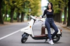 Casual young woman sitting on moto scooter on narrow street in town. Stock Photo