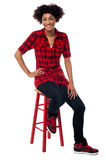 Casual young woman sitting on stool Royalty Free Stock Photo
