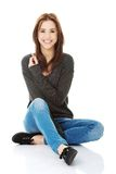Casual young woman sitting on white floor Stock Photography