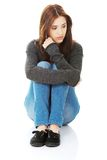 Casual young woman sitting on white floor royalty free stock photo